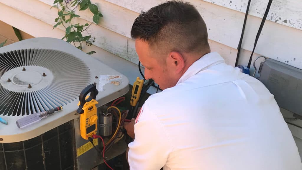 Our technician works on an air conditioner as part of our fast, reliable AC repair service here in Western New York.