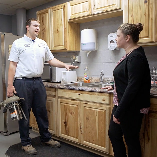 One of our helpful plumbers talks to a Cheektowaga homeowner about their new in-sink garbage disposal.