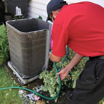 A Reimer technician uses a hose to clean the outside of an AC unit here in Buffalo, NY.