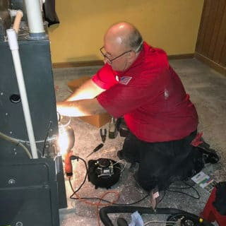 One of our experienced techs uses a work light to see inside of this furnace as part of an inspection and tune-up.