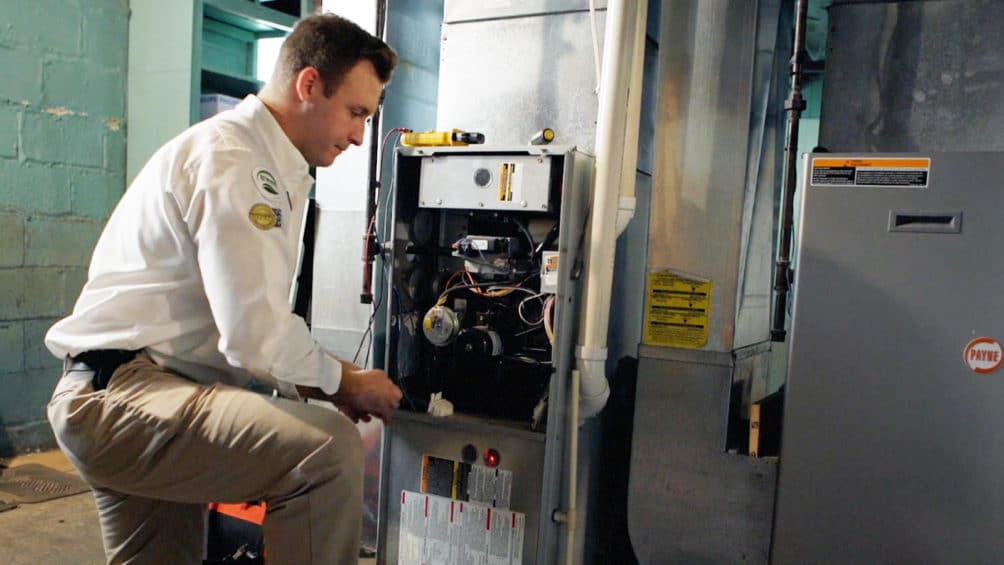 A Reimer technician kneels next to a furnace as they put the finishing touches on a new furnace install.