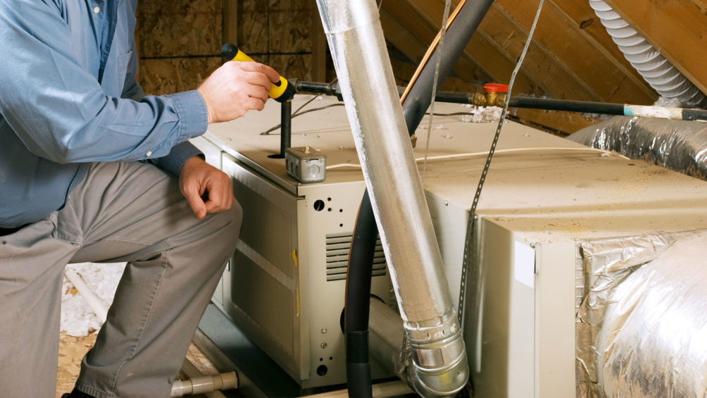 Our technician works on this gas furnace, located in this home's attic, to ensure that it's running right.