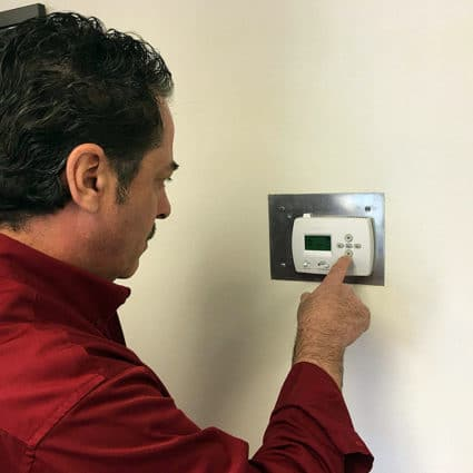 One of our techs checks that the thermostat is working properly as part of our heater tune-up in Tonawanda.
