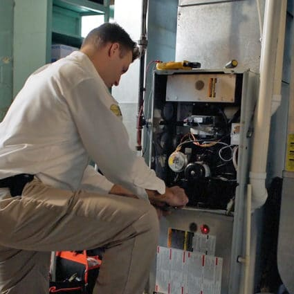 A Reimer heating repair specialist works on a furnace as part of our heating repair in Tonawanda, NY.