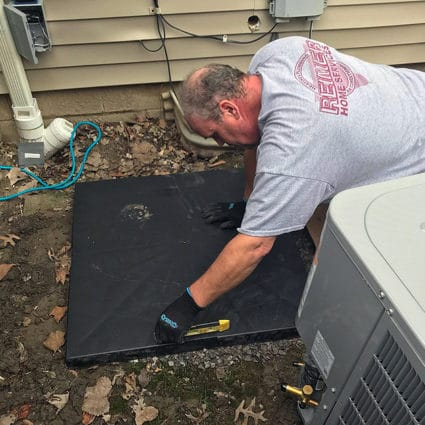 A Reimer technician ensures that the AC concrete pad is completely level before moving forward with installation.