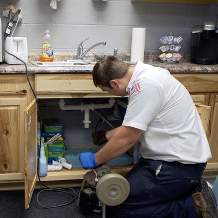 Our plumber uses a specialized snake tool to clear out a tough clog in this business' kitchen sink.