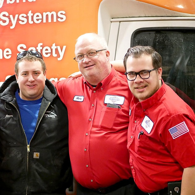 Three of our plumbers pose for a picture in front of our famous orange service vehicle.