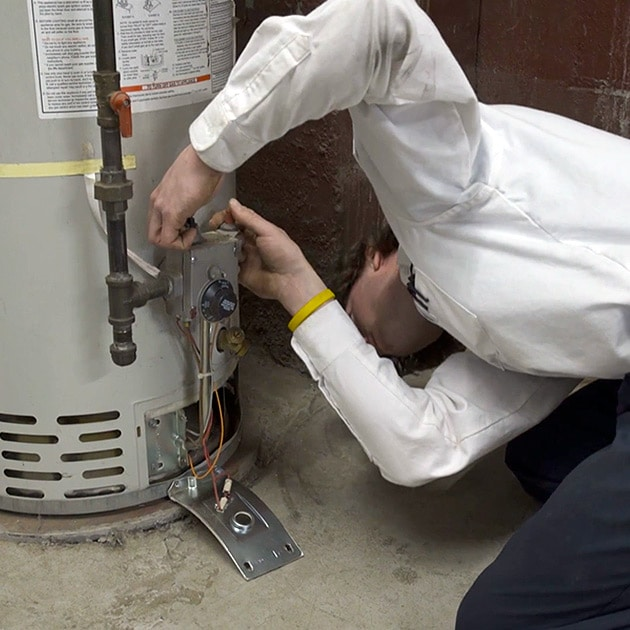 A Reimer plumber looks at the heating element of a water heater here in Buffalo, NY.